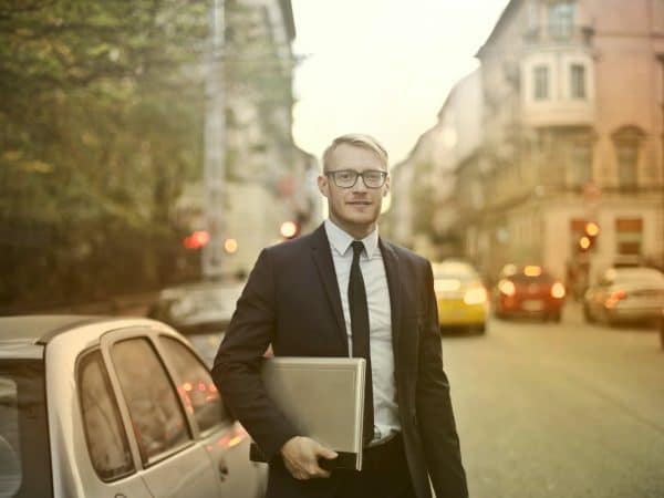 determined smiling businessman with laptop on street